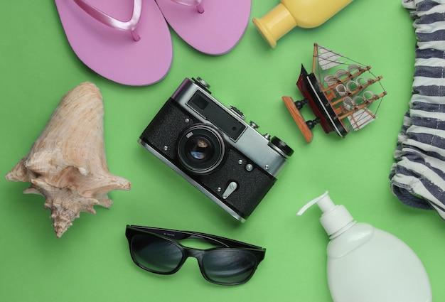 Letnia martwa natura. akcesoria plażowe. modne różowe klapki, torba, aparat retro, butelka z filtrem, okulary przeciwsłoneczne, muszla na zielonym papierze