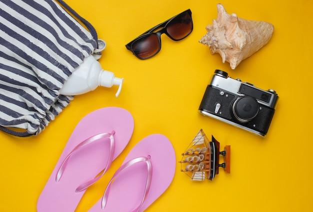 Letnia martwa natura. akcesoria plażowe. modne różowe klapki, torba, aparat retro, butelka z filtrem, okulary przeciwsłoneczne, muszla na żółtym tle papieru.