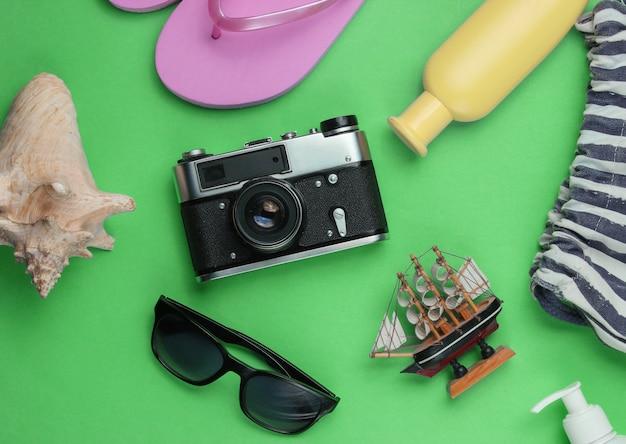 Letnia martwa natura. akcesoria plażowe. modne różowe klapki, torba, aparat retro, butelka z filtrem przeciwsłonecznym, okulary przeciwsłoneczne, muszla na zielono