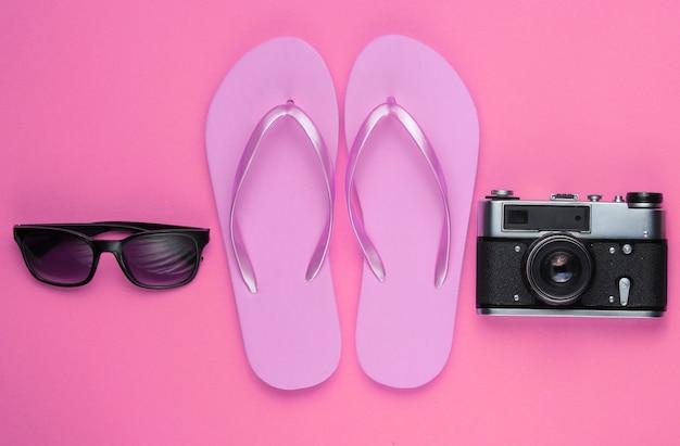 Letnia martwa natura. akcesoria plażowe. modne różowe klapki, torba, aparat retro, okulary przeciwsłoneczne, statek na różowo