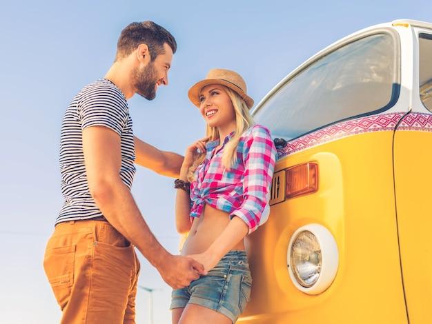 Letnia miłość. niski kąt widzenia szczęśliwej młodej pary trzymającej się za ręce i patrzącej na siebie, stojąc w pobliżu swojego retro minivana