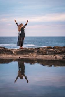 Letnia młoda brunetka kaukaska kobieta w długiej czarnej przezroczystej sukni na niektórych skałach w pobliżu morza w letnie popołudnie. podnoszenie rąk nad morzem