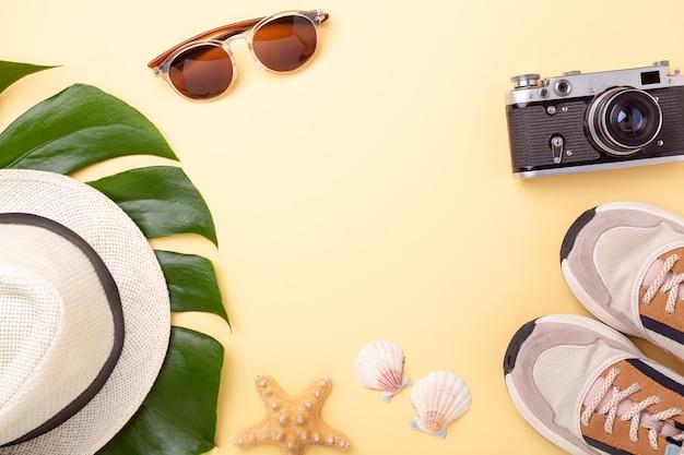 Letnia moda leżała płasko. gałęzie monstera, okulary przeciwsłoneczne, trampki, kapelusz i aparat retro
