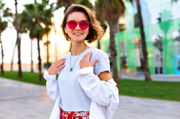 Letnia moda na zewnątrz jasny portret stylowej modnej uśmiechniętej kobiety noszącej stylowy strój hipster, białą dżinsową kurtkę i neonowe okulary przeciwsłoneczne, dłonie wokół, szczęśliwy podróżniczy nastrój.