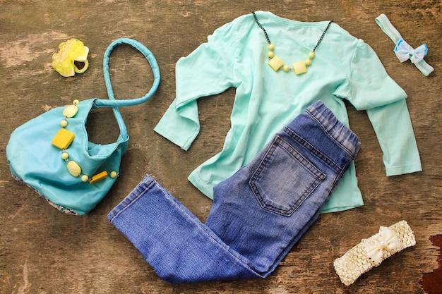 Letnia odzież dziecięca: t-shirt, jeansy, torebka, koraliki. widok z góry.