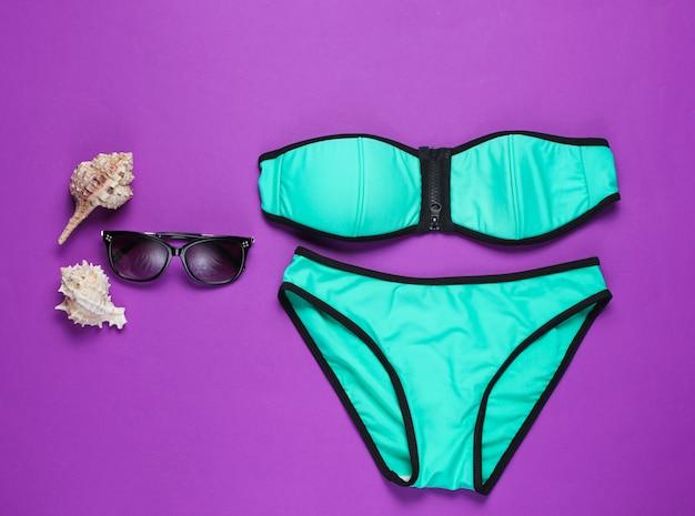 Letnia odzież plażowa i akcesoria na fioletowej powierzchni.