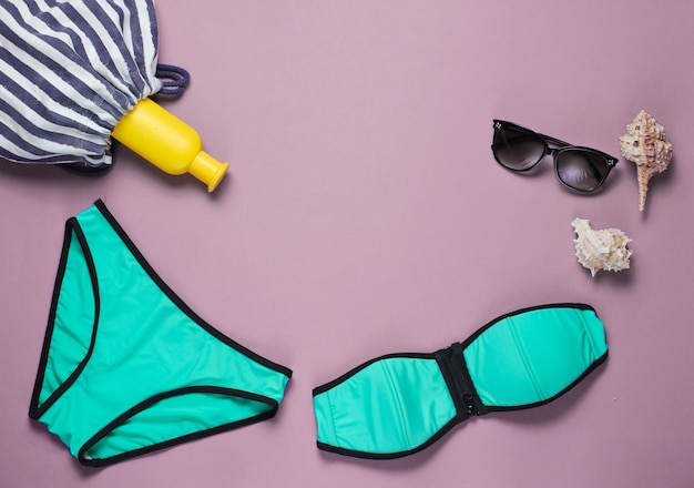 Letnia odzież plażowa i akcesoria na różowo. strój kąpielowy damski, okulary przeciwsłoneczne, torba plażowa