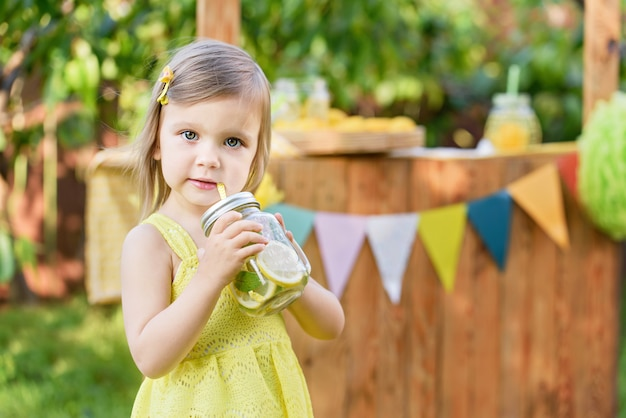 Letnia orzeźwiająca naturalna lemoniada. mała dziewczynka napoju naturalna lemoniada przy lemoniada stojakiem w parku.