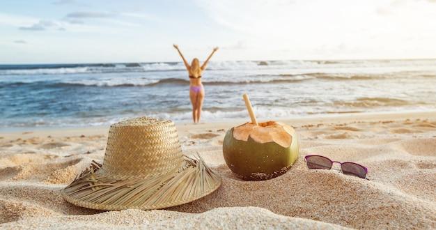 Letnia panorama dziewczyna spaceruje po plaży w rozmytym tle kokosowy kapelusz i okulary przeciwsłoneczne leżą na piasku zbliżenie