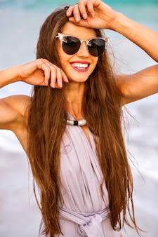 Letnia plaża portret ładnej brunetki kobiety o sportowym, idealnie opalonym ciele i długich włosach brunetki, ubrana w modny elegancki strój kąpielowy, modelka relaksująca się w pobliżu oceanu, okulary przeciwsłoneczne i biżuteria.