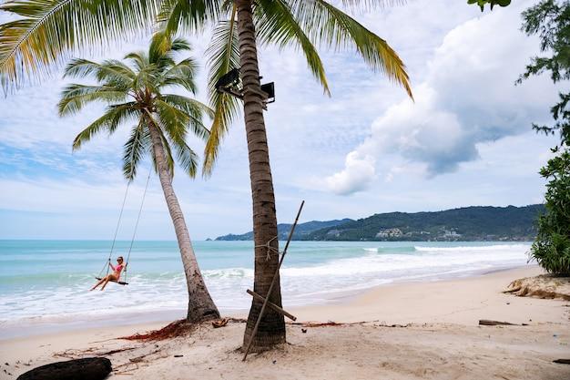 Letnia plaża z palmami wokół w patong beach phuket island tajlandia, piękna tropikalna plaża z błękitnym niebem w sezonie letnim.