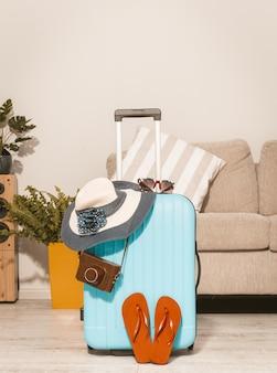 Letnia podróż, walizka z havaianas i czapką.