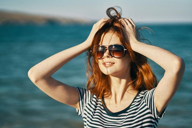 Letnia podróżniczka na plaży w pobliżu morza, dotykając głowy rękoma przycięty widok