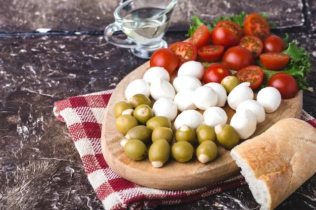 Letnia przekąska z mozzarellą, pomidorami, oliwkami i zieleniną na desce, kawałek bagietki, oliwa z oliwek i serwetka w czerwoną kratkę. brązowe tło