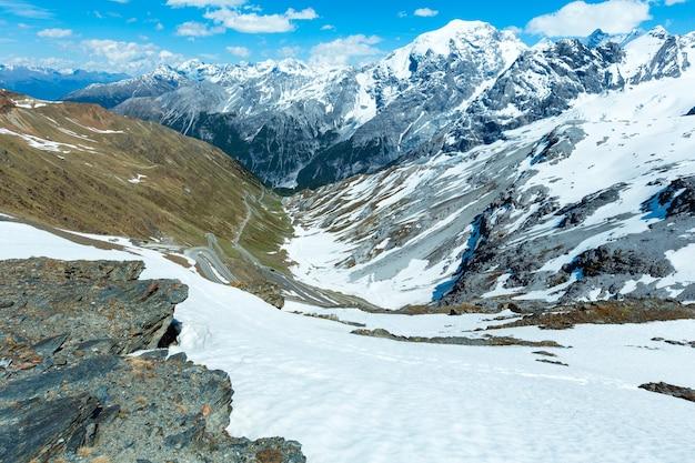 Letnia przełęcz stelvio z alpejską drogą i śniegiem na zboczu (włochy)