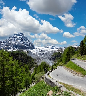 Letnia przełęcz stelvio z lasem jodłowym i śniegiem na szczycie góry (włochy). dwa strzały obrazu ściegu.