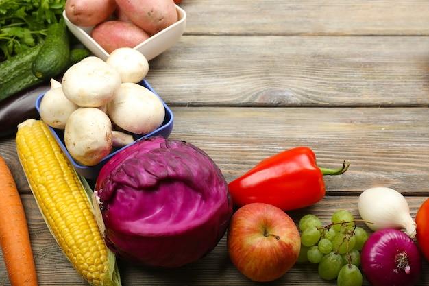 Letnia ramka ze świeżymi organicznymi warzywami i owocami na drewnianej ścianie