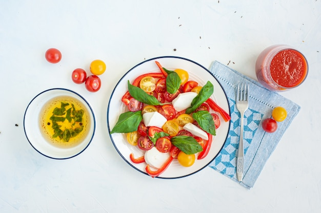 Letnia sałatka jarzynowa z serem i bazylią. sos i sok pomidorowy w szklance.