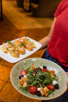 Letnia sałatka na białym talerzu z kelnerem w ręku.