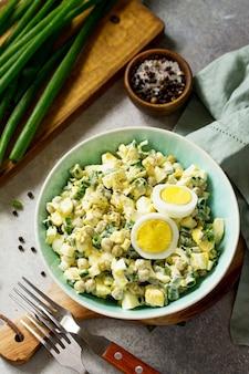 Letnia sałatka witaminowa z jajkiem i zielonym groszkiem na jasnym stole z kamienia lub łupka styl rustykalny