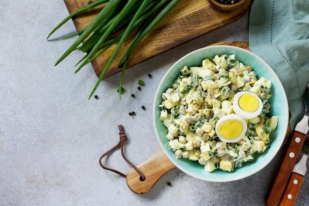 Letnia sałatka witaminowa z jajkiem i zielonym groszkiem na jasnym stole z kamienia lub łupka widok z góry