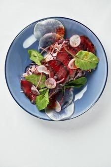 Letnia sałatka z buraków z rukolą, radicchio, miękkim serem i orzechami włoskimi na sosie talerzowym i przyprawami na niebieskim talerzu, miejsce na kopię, widok z góry.
