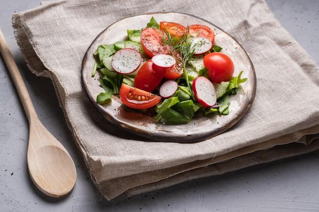 Letnia sałatka ze szpinaku, pomidorów, rzodkiewki, koperku na szarym tle