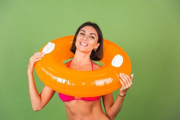 Letnia sportowa kobieta w różowym bikini i jasnopomarańczowym nadmuchiwanym pierścieniu okrągłym na zielonym, szczęśliwa wesoła podekscytowana radosna pozytywna