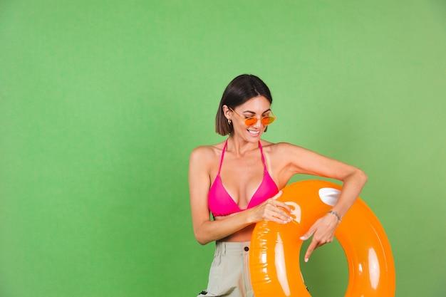 Letnia sportowa kobieta w różowym bikini i jasnopomarańczowym okrągłym nadmuchiwanym pierścieniu i okularach przeciwsłonecznych na zielonym, szczęśliwa wesoła podekscytowana radosna pozytywna