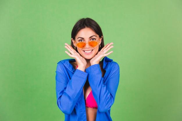 Letnia sportowa kobieta w różowym bikini, niebieskiej koszuli i pomarańczowych okularach przeciwsłonecznych na zielonym, szczęśliwa wesoła radosna pozytywna