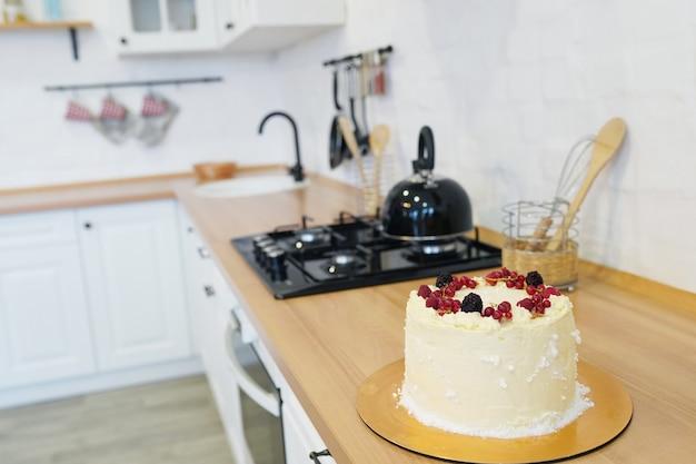 Letnia tarta z kremem budyniowym, świeżą wiśnią i truskawką na drewnianym stole w kuchni