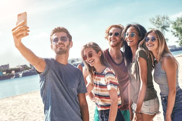 Letnia turystyka morska technologia i grupa ludzi koncepcja grupy uśmiechniętych przyjaciół ze smartfonem na plaży