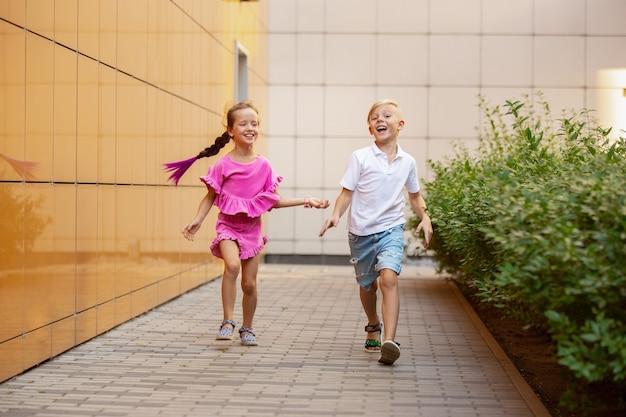 Letnia wigilia dwoje uśmiechniętych dzieci, chłopiec i dziewczynka biegają razem w mieście w letni dzień