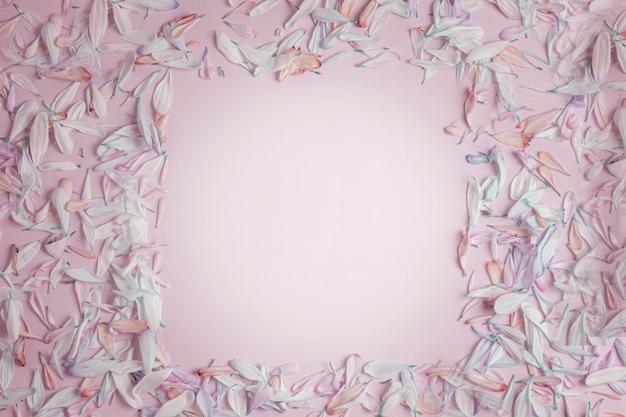 Letnia wiosenna kwadratowa ramka z płatkami kwiatów w różowych odcieniach, na kremowym różowawym matowym