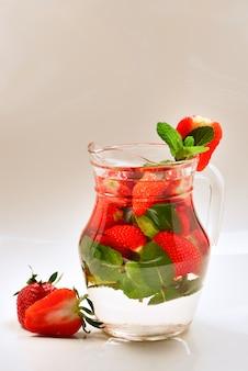 Letnia woda aromatyzowana o smaku świeżych owoców z truskawek i mięty. miejsce na testy lub projekt.