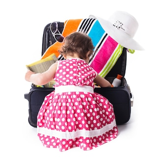 Letnia wyprawa z dziećmi - maluch pomaga wkładać do torby akcesoria do powołania