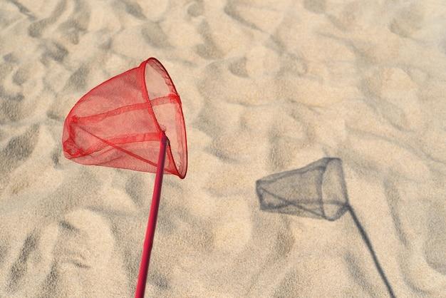 Letnia zabawa dla dzieci. rozrywka na piaszczystej plaży nad morzem. siatka na czerwone motyle do łapania motyli i ryb