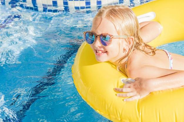 Letnia zabawa. dosyć małej dziewczynki dopłynięcie w plenerowym basenie