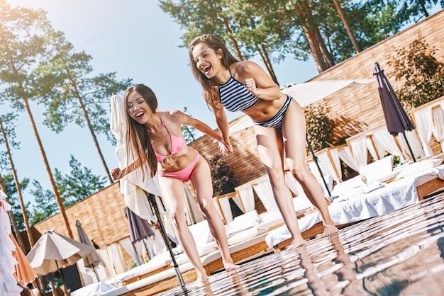 Letnia zabawa dwie piękne i zabawne młode kobiety w stylowych strojach kąpielowych, śmiejące się i skaczące do środka