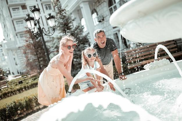 Letnia zabawa. matka, ojciec i córka śmieją się i myją ręce w fontannie na zewnątrz.