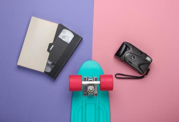 Letnia zabawa. młodzież leżała płasko. deska cruiser z kamerą retro, kaseta wideo na różowo fioletowym kolorze.