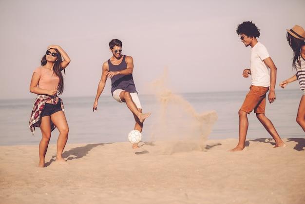 Letnia zabawa z przyjaciółmi. grupa wesołych młodych ludzi bawiących się piłką nożną na plaży z morzem w tle