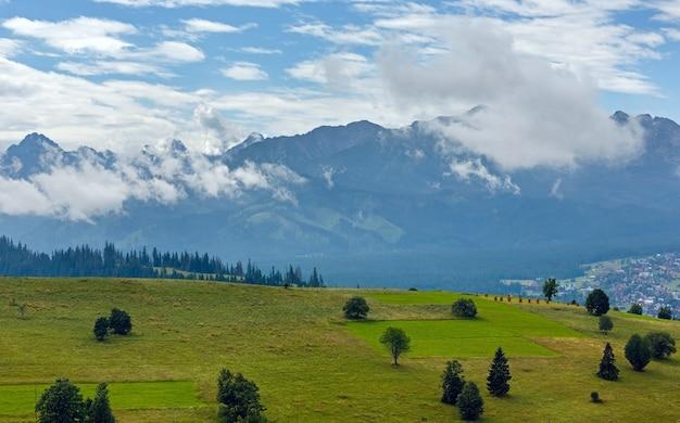 Letnia zamglona górska wieś na przedmieściach z pasmem tatr