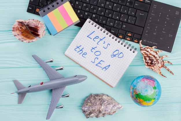 Letnie akcesoria podróżnicze składają się z muszelek, samolotu, kuli ziemskiej na niebieskim tle. przejdźmy do sea na notebooku.
