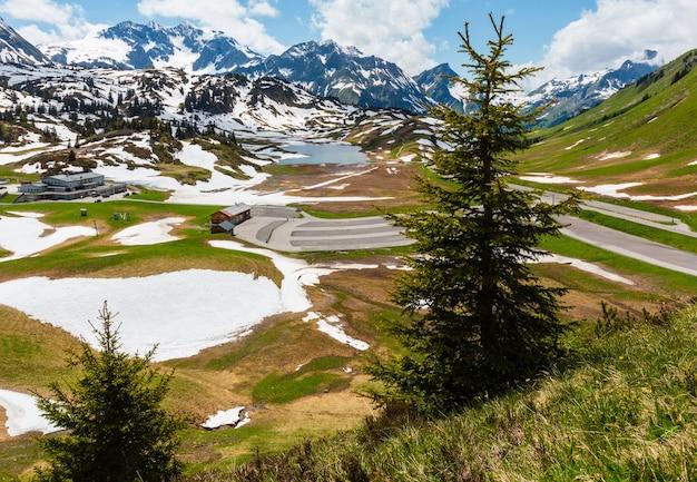 Letnie alpy z widokiem na małe jezioro kalbelesee i parking przy przełęczy hochtannberg i łące, na której roztapia się śnieg (warth, vorarlberg, austria).