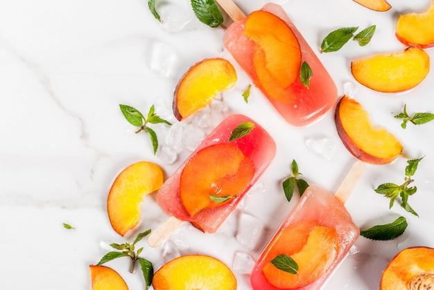 Letnie desery. mrożone napoje słodkie owoce popsicles z mrożonej brzoskwiniowej herbaty z miętą. na białym marmurowym stole, ze składnikami brzoskwinie, mięta, lód. widok z góry