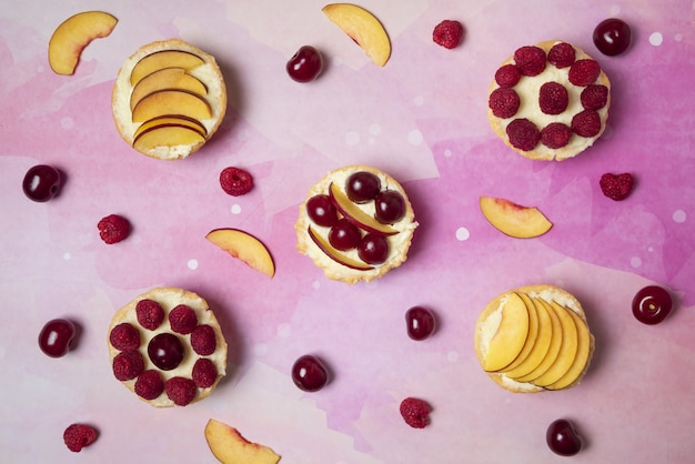 Letnie desery z pokrojonymi owocami i jagodami na różowym tle