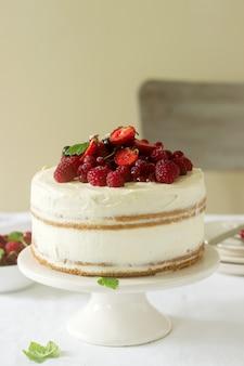 Letnie domowe ciastko z kremem twarogowym, ozdobione świeżymi jagodami truskawek, malin i porzeczek.