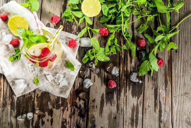 Letnie drinki, koktajle. wegańskie jedzenie. naparowana woda detoksykacyjna z limonką, miętą i świeżymi malinami organicznymi
