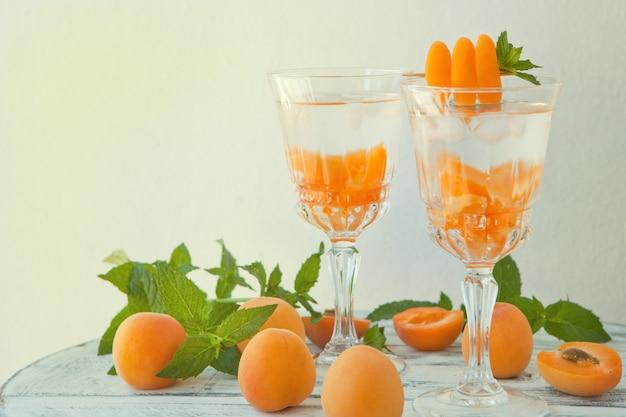 Letnie drinki, miętowe koktajle morelowe z lodem w szklankach. orzeźwiające letnie domowe koktajle alkoholowe lub bezalkoholowe lub woda smakowa z detoksem